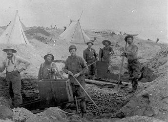 black and white photo of six men standing with mining equipment