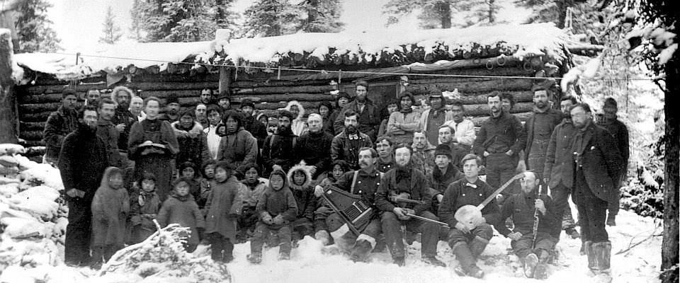 black and white photo of men in winter parkas in front of a cabin