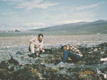 two men kneeling on the ground working