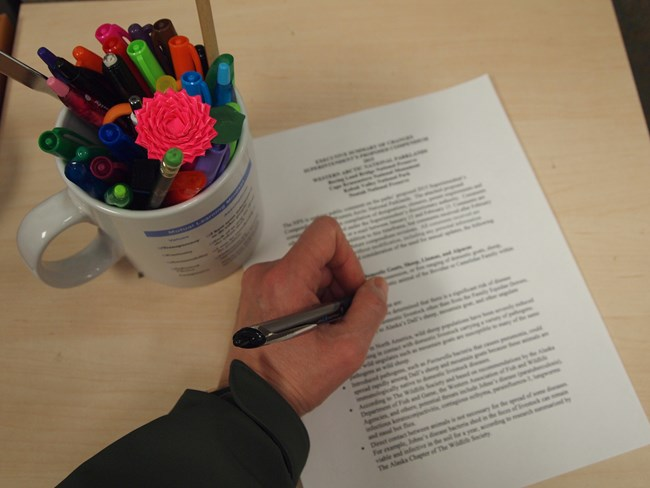 hand with pen over a printed compendium with cup of writing utensils
