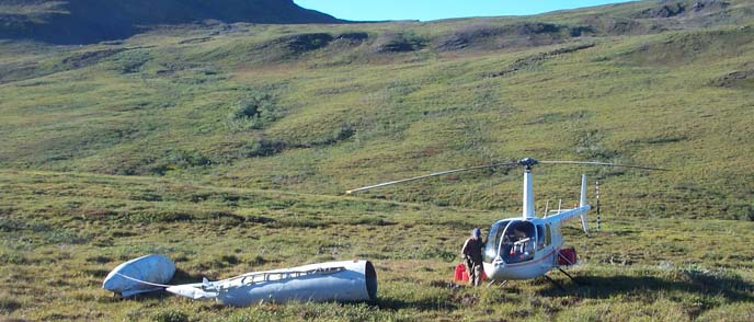 Image of hilly tundra and a helicopter preparing to remove an abandoned fuel pod