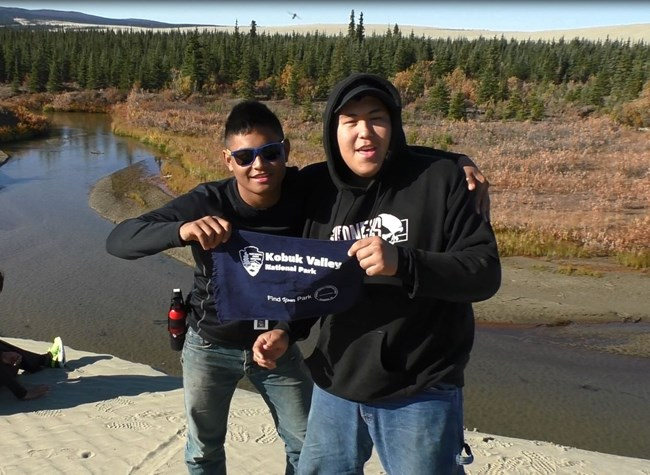 "Two visitors hold up a Kobuk Valley National Park sign and record their ""Find Your Park"" video postcard"