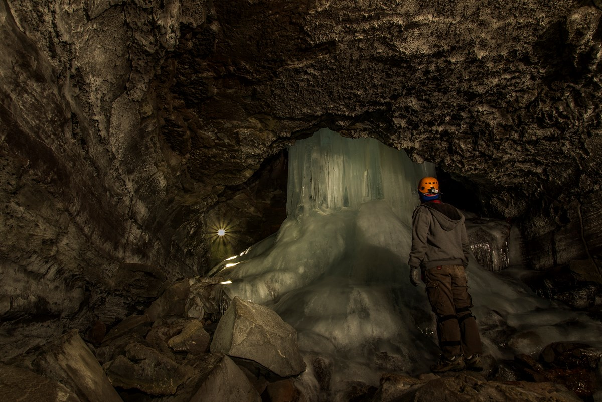 A visitor explores ice features in Crystal Ice Cave