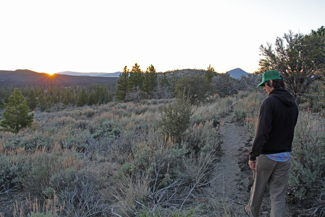 Visitor hiking along the Big Nasty Trail at sunset.