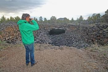 A visitor scans the lava tube collapse along the Heppe Cave Trail (cave entrance seen in the distance).