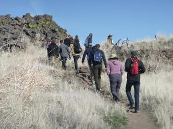 A group of visitor's hikes uphill through Captain Jack's Stronghold