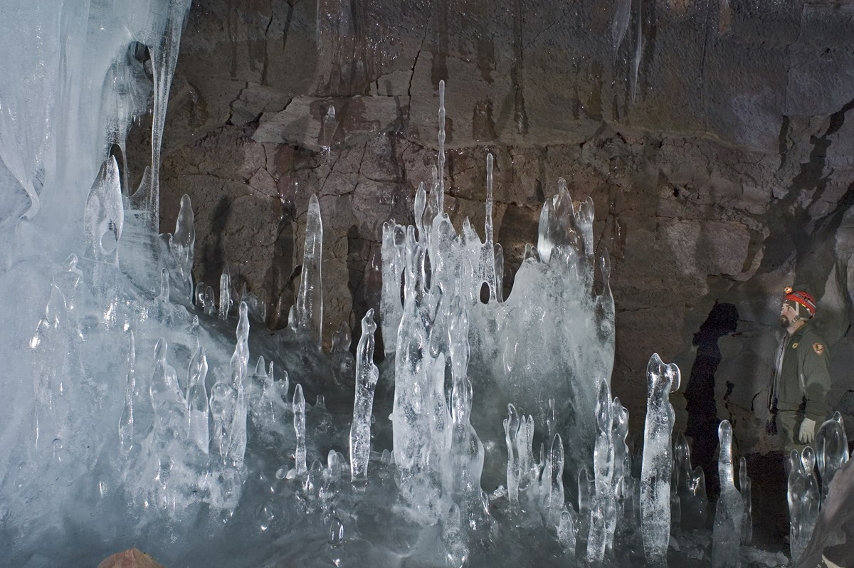 A visitor stands next to towering ice formations in Crystal Ice Cave