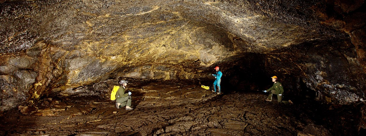 NPS staff surveys a wide passage in Golden Dome Cave for microbial life.