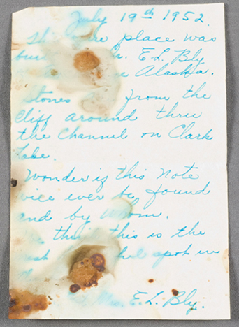 handwritten note in blue ink on unlined paper. The note is blotched with what appears to be water stains.