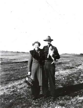 black and white image of a man and woman posing in a field, holding a small dog