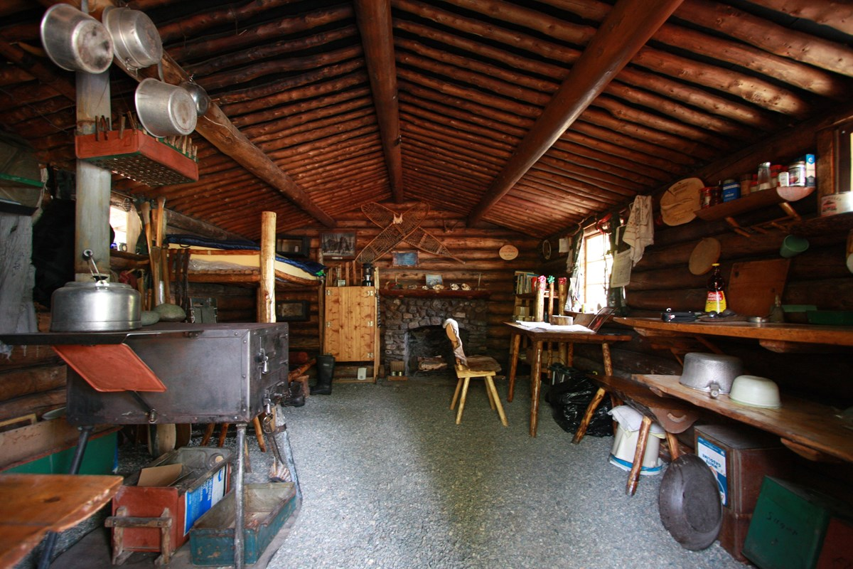 A wooden cabin interior with fireplace, wood stove, furniture and hanging pots