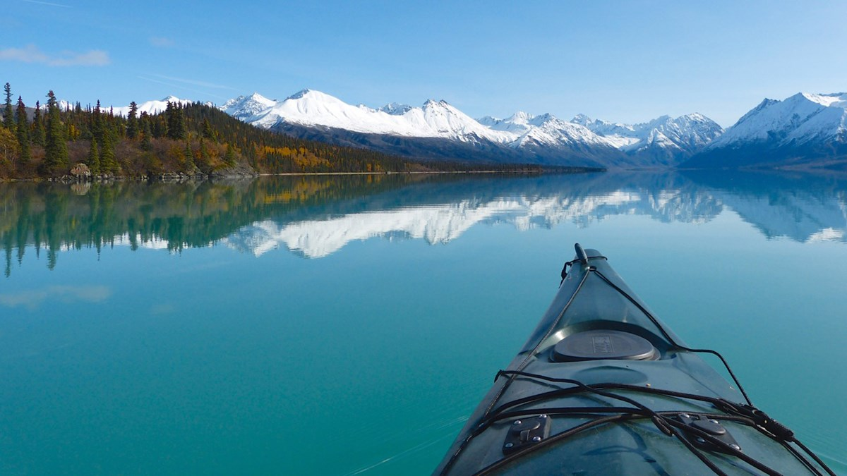 A kayaker's view of mountains reflecting in a calm turquoise lake