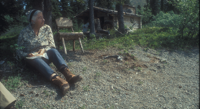 a woman and man sitting near a log cabin
