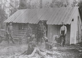 historic image of four men and a few dogs in front of a log cabin with a sheet metal roof