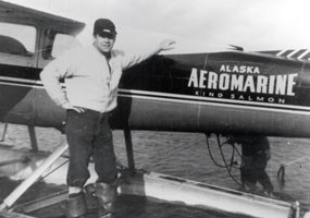 historic, black and white photo of a man standing next to a float plane.