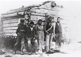 Historic black and white photo of seven Alaska natives in front of a rough-hewn cabin.