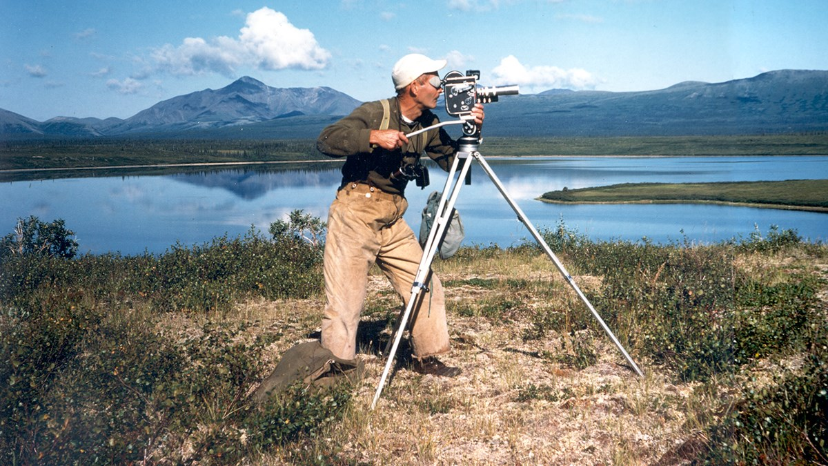 Photo of a man standing in profile filming with an old-fashioned movie camera on a tripod. In the background there is a blue lake and distant mountains.