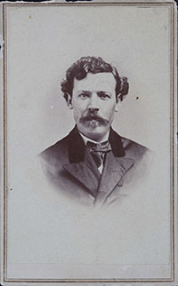 black and white head shot photo of a man with curly hair and a mustache wearing a suit.