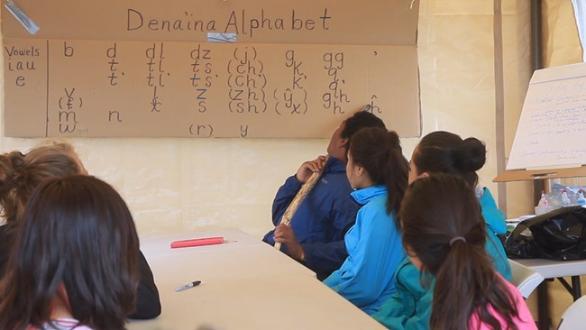 "Students sit at table with cardboard sign reading ""Dena'ina Alphabet"""