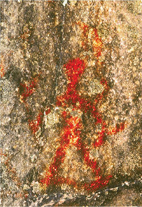 A red ochre pictograph of a human figure, with legs, somewhat relaxed, joined by a thin line, holds what appears to be two rattles.