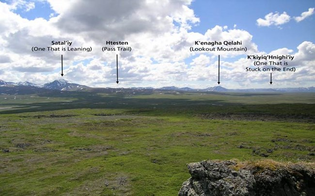 tree-less green plain leading up to mountains, with four points called out in text.  from left to right, one that is leaning, pass trail, lookout mountain, one that is stuck on the end