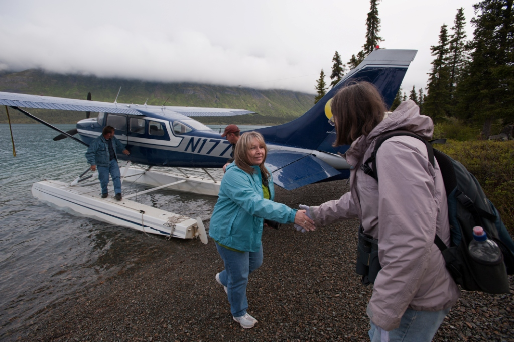 Women shaking hands with blue and white float plane in the background. Two other people are standing on the floats of the plane.