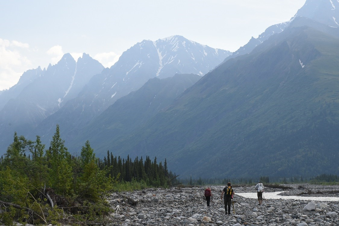 Three hikers walk along a gravel river bed with misty mountains in the background