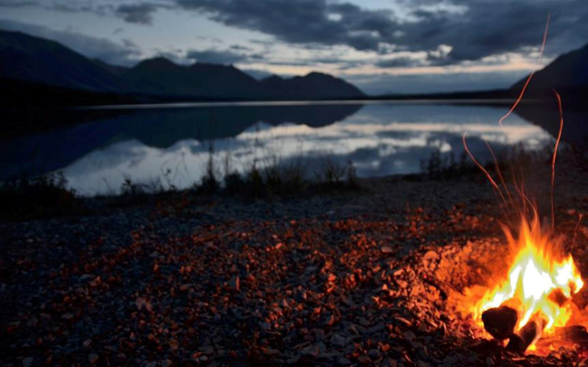A campfire burns on a beach in the right, bottom corner of the photo with a lake and mountains at dusk in the background.