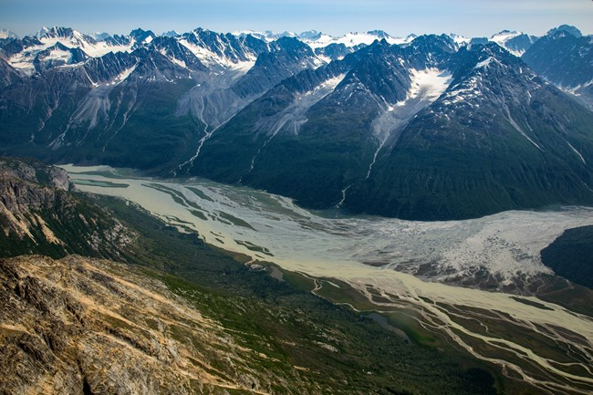 a braided river cuts through jagged mountains with glaciers at the top