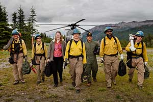 eight people in mostly-yellow uniforms walking away from a helicopter, mountains in the distance