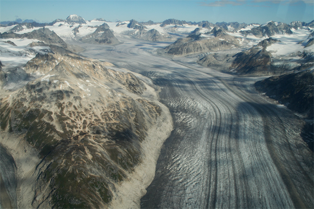 aerial view of a massive glacier, striated white and brown