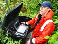 man in an orange rain coat sets up a computer and other equipment outdoors