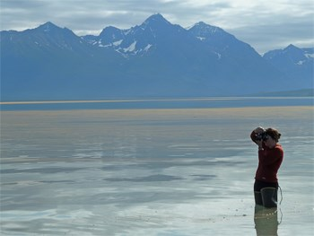 person in hip waders standing in a lake, taking a picture; mountains in the distance