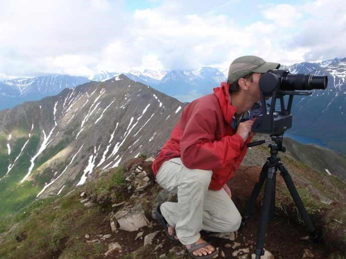 A man shoots photographs from a mountain top with mountains in the background.