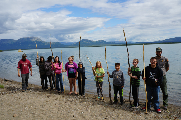 Middle School and High School age students, a park ranger, and an archeologist stand by a lake with mountains in the background.  Students have long spears in their hands.