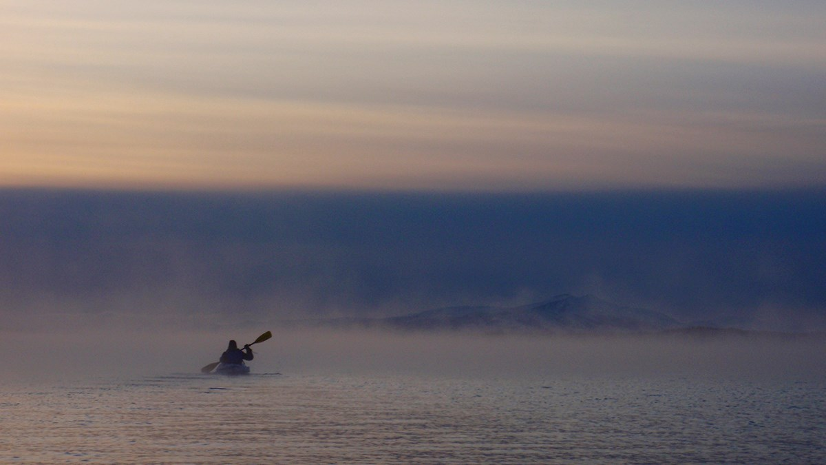 One person kayaking across a foggy lake with steam rising off the water.