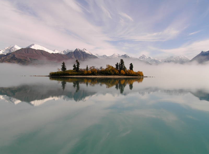 mist rising around a small island in a lake, with snowy mountains in the distance