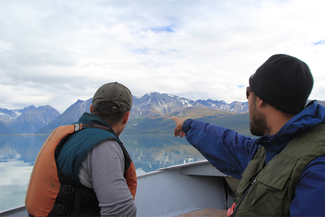 Two men look at something from a boat on Lake Clark.