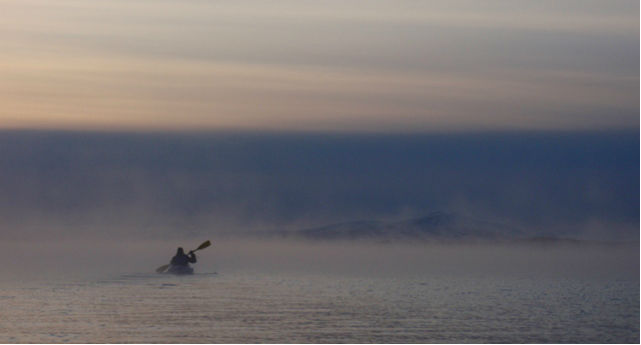 person kayaking across a foggy lake, steam rising off the water