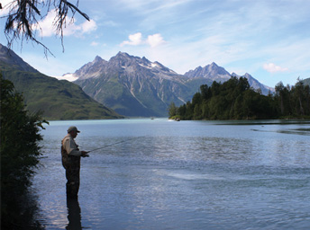 man fishing in a lake, surrounded by forest and tall mountains