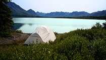 White tent overlooks lake surrounded by mountains.