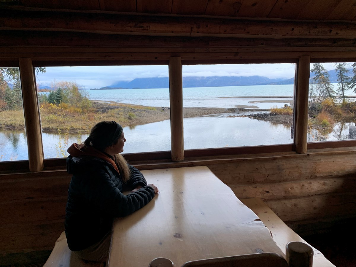 a woman sitting at a table looks out the cabin windows to the lake outside