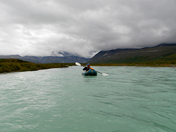 photo of a person paddling down a river in an inflatable raft with heavy clouds overhead.