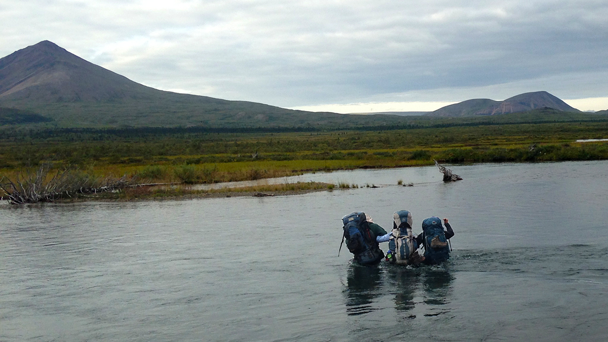 Photo of three people wearing large backpacks linked arm-to-arm crossing a wide, waist-deep river with small mountains in the background.