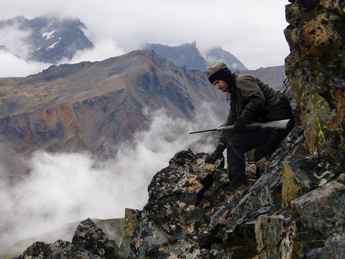 man with a rifle navigating steep mountain terrain on a foggy day