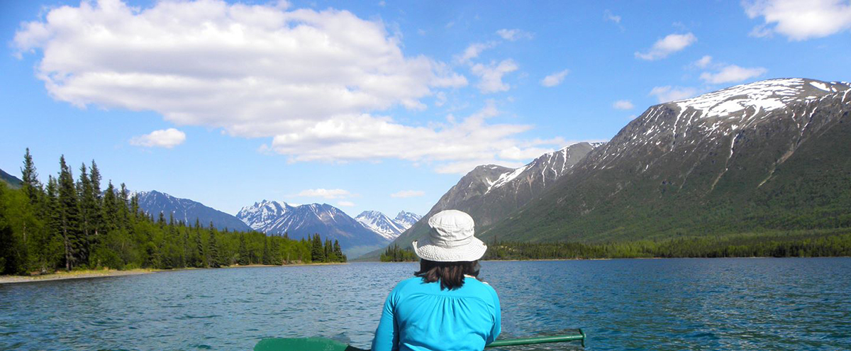 Photo of a woman sitting in a canoe with a paddle in her lap facing away from camera as she looks out over a lake bound by snow capped mountains.