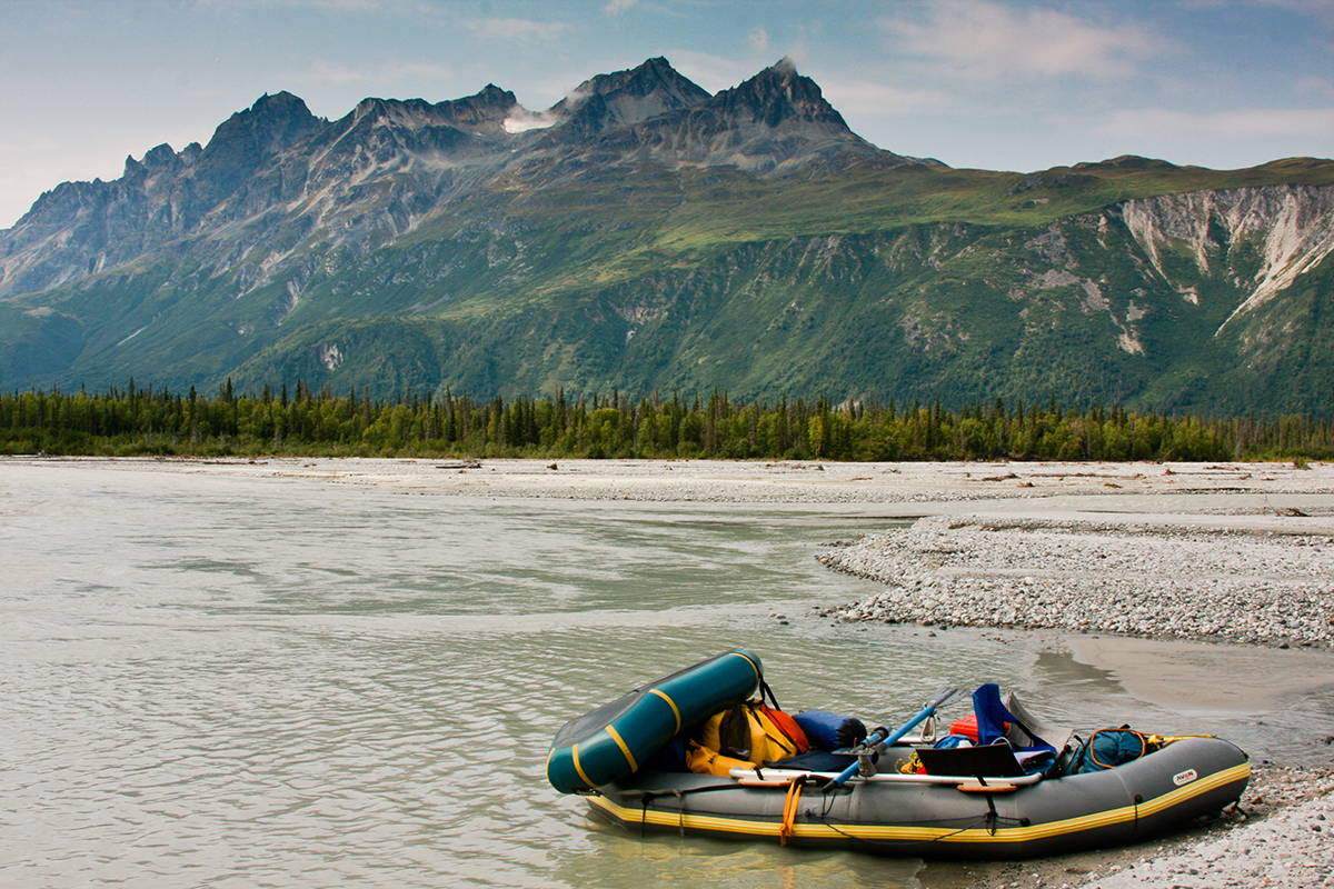Photo of an inflatable raft loaded with equipment resting on a gravel bar. Tall forested mountains dominate the background.