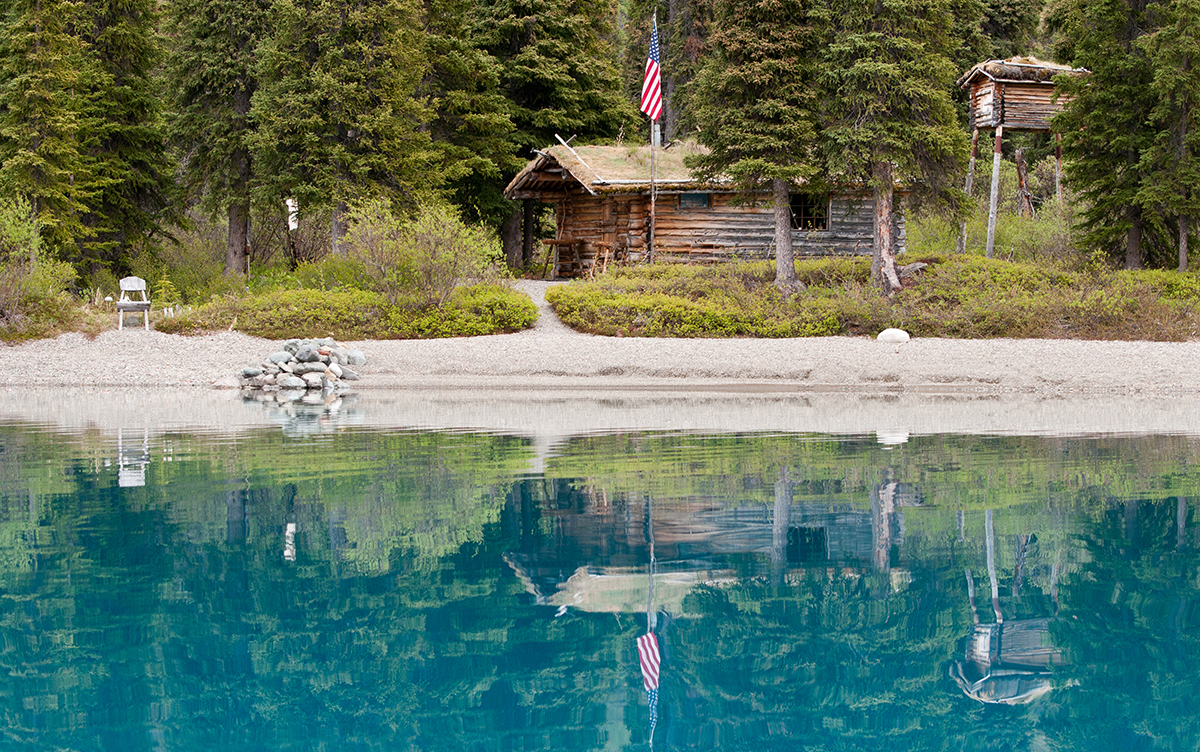 photo of a log cabin tucked into a spruce forest reflecting in a blue lake.