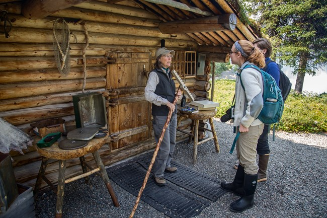 a park volunteer talks to visitors in front of the Proenneke cabin