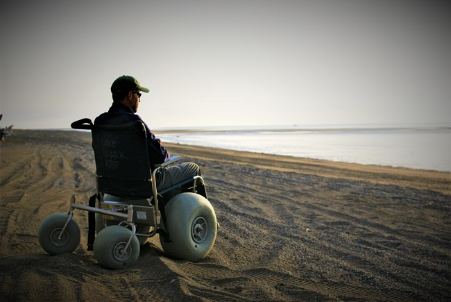 a man sits in a dune buggy wheelchair on a sandy beach